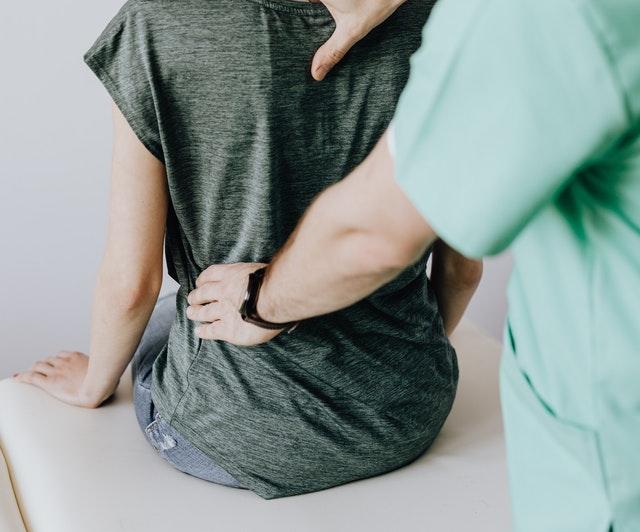 Rehabilitant ustalający zdrowie kręgosłupa w spoczynku.